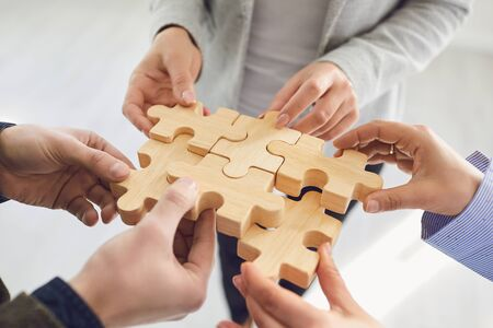 Business people holding wooden gears in their hands connect at a business meeting in the office. Concept of partnership creative work startup startup teamwork team business people. Banque d'images