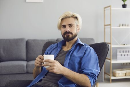 Online video chat. A young man in casual clothes with a mug of coffee looks at the camera while sitting in an armchair in a living room. The guy speaks with friends using the video call chat application remotely.