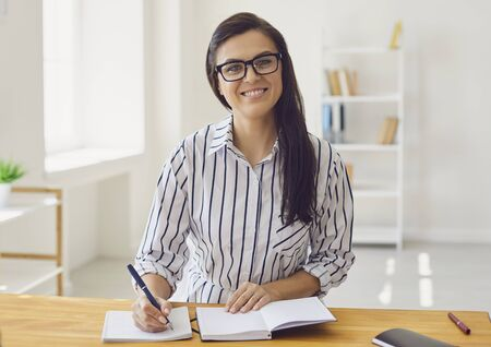 Hispanic teacher with glasses looking at the camera smiling. Teaches a lecture while sitting at the table. Online learning. A college university teacher teaches remotely using a video call application gadget. Imagens
