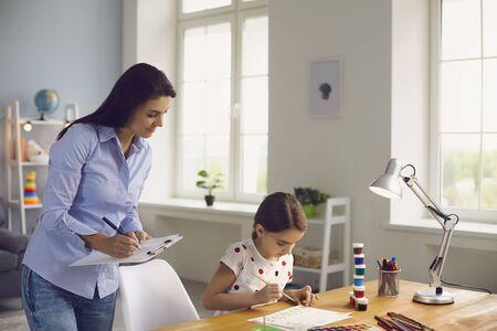 Psychologie des Kinderpsychologen. Eine Psychologin mit einer Zwischenablage arbeitet mit einem kleinen Mädchenpatienten in einem Kinderzimmer. Die psychologische Betreuung von Kindern mit Aufmerksamkeitsdefizitstörung durch einen Spezialisten.