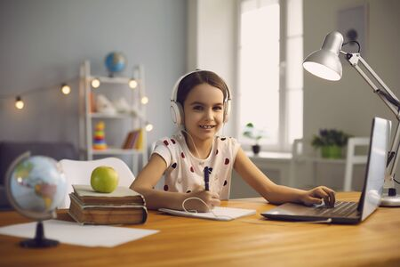 Online training. The teacher teaches the child a video call chat classroom video conferencing. Little girl teach a lesson using a laptop with sitting at a table at home. Education school remotely online internet educational video lecture. Stock fotó