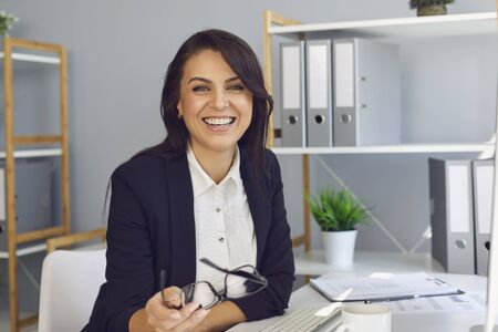 Happy adult woman in formal wear holding glasses and smiling for camera while sitting at table and working in modern office Standard-Bild