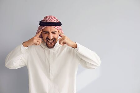 Arabic man shouting holding hands to head on a gray background.