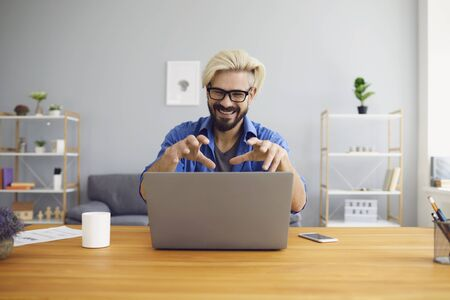 Bearded guy in glasses smiling and gesticulating while sitting at table in home office and making video call to colleague