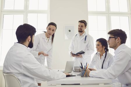 Group of practicing doctors in a meeting discuss the diagnosis of a patient sitting at desk in a clinic office. Confident doctors at the conference talking. Фото со стока
