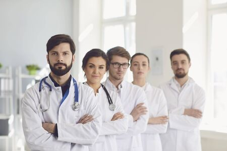 A group of confident practicing doctors cross arms in white coats are smiling against the backdrop of the clinic. Doctors team in a medical hospital.