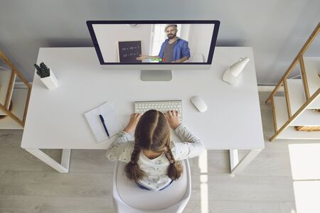 Online learning lessons education school. Litle girl are doing online education with a teacher using a laptop sitting at a desk at home. Zdjęcie Seryjne
