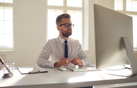 Work online. Serious busy businessman in glasses in a white shirt working sitting at a table with a computer in the office.