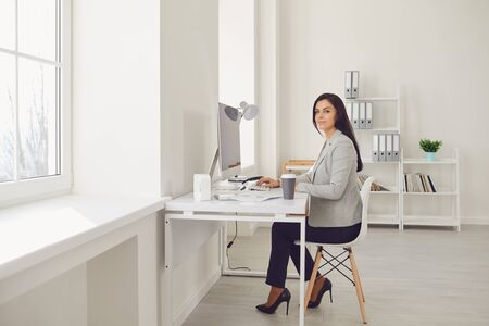 Beautiful busy serious business woman in a gray jacket looks sitting at a workplace at a table in a white office. Foto de archivo
