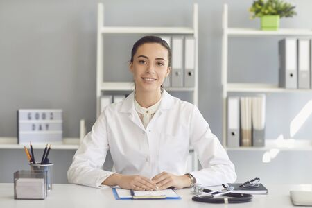 Positive doctor woman looking at the camera smiling while sitting at a table in a clinic office. Фото со стока
