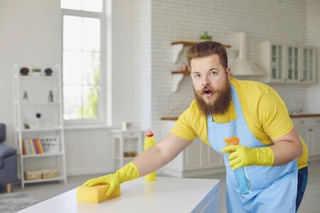 Funny fat man with a beard in an apron cleans the room in the house. A cleaner man washes an apartment. Cleaning service office home apartment. Stock fotó