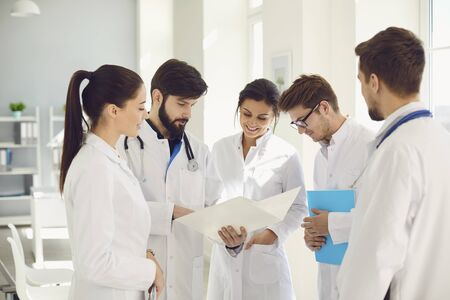 A team of doctors in a meeting discusses the diagnosis of a patient in a clinic office. Teamwork of doctors at the conference of colleagues in the hospital. Profession practicing doctor.