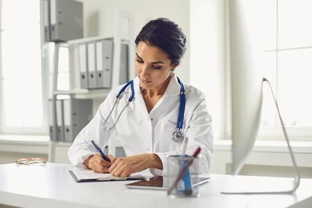Confident woman doctor pediatrician writes in a clipboard sitting at a table in a white office of the hospital.