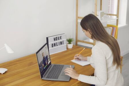 Work online. The remote employee has a video chat call using a laptop on a desk not in the workplace at home. A businesswoman in casual clothes works in a living room. 스톡 콘텐츠