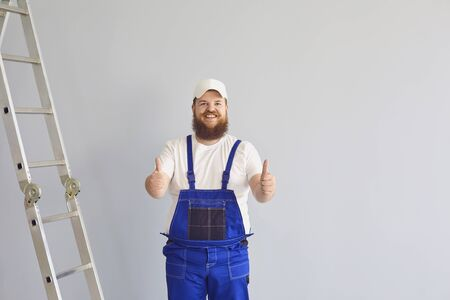 Positive male constructor wearing overalls showing thumbs up gesture while standing near stainless steel ladder in empty room and looking at camera