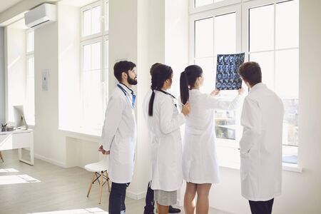 A group of doctors looks at a x-ray photo while standing in a hospital office. A team of doctors in a meeting discusses the diagnosis of a patient in a clinic office. Profession practicing doctor.