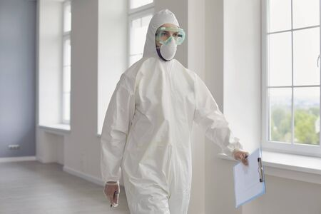 Doctor in protective wear, glasses and gloves walking along hospital hall. Medic in hazmat suit fighting with contagious disease at clinic