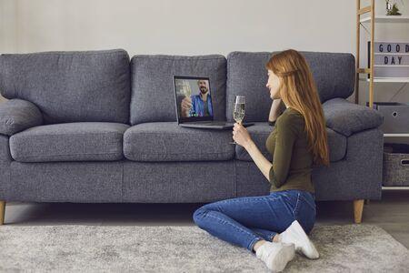 距離通信の概念。自宅からオンラインでボーイフレンドと話しているかわいい若い女性、シャンパンのグラスで記念日や誕生日を祝う、コピースペース