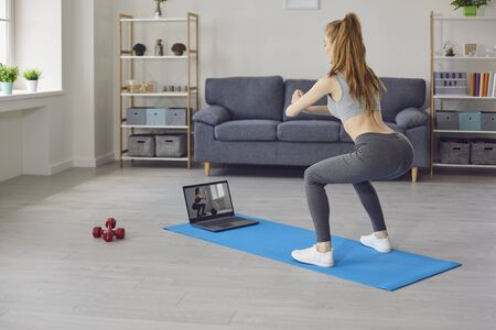 Online sports concept. Red haired girl watching video training on laptop computer and doing squats in living room, space for your text