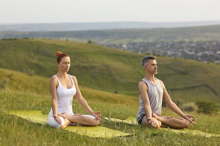 Practice yoga meditation. A mated couple practices yoga meditation in lotus position sitting on the grass on the nature of the countryside in summer spring.