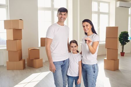 Happy family with keys in their hands stands in a new house. The concept of moving estate new apartment house move home buy sale property rent room investment .