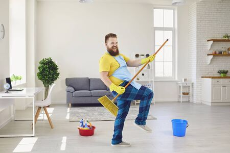 Side view of childish male in apron and rubber gloves pretending playing guitar while standing with cleaning brush in living room and looking at camera.