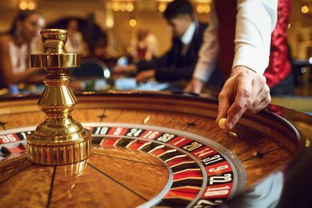 Hand eines Croupiers mit einer Kugel auf einem Roulette-Rad während eines Spiels in einem Casino. Glücksspiel-Konzept.