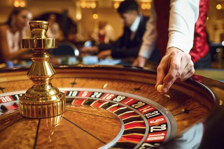 Hand of a croupier with a ball on a roulette wheel during a game in a casino. Gambling concept. Stock fotó