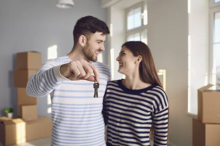Happy couple with keys to new home in hands smiling while standing in room. Concept of buying sale rent moving selling house rental mortgage investment in new home apartment real estate.