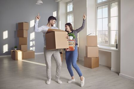 A cheerful couple is playing with a moving box in a bright room of a new house. Concept of buying sale rent moving selling house rental mortgage investment in new home apartment real estate. Reklamní fotografie