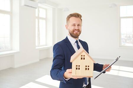 Male real estate agent holding a model of the house smiling while standing in white real estate room apartment home. Reklamní fotografie