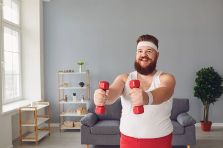 Funny fat man with dumbbells in sportswear doing exercises in the room. Red bearded fat man has fun doing exercises indoors interior.