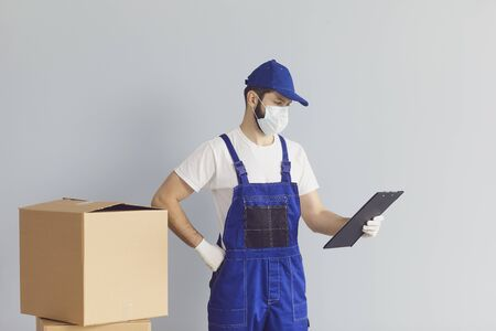 Delivery man in protective mask with carton parcels against grey background. Male courier shipping internet order during epidemic Banco de Imagens