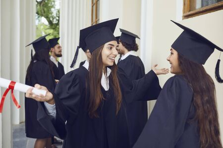Female graduates with diplomas in their hands hugging laugh at the background of the education, Graduation.University gesture and people concept. 写真素材