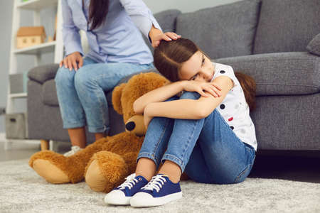 The problem is the relationship between mother and child in the family. Conflict concept angry resentment ignore child depression. Sad offended child sitting on the floor does not talk with mother in the room.