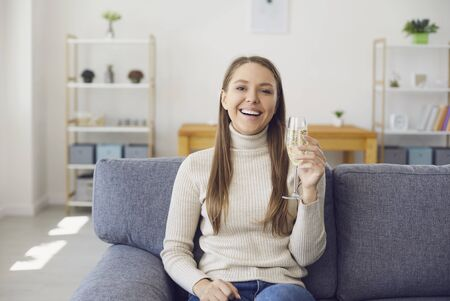 Girl with a glass of wine looks at the camera smiling at home. A young woman drinks wine from a glass while sitting on a sofa in the room. 写真素材