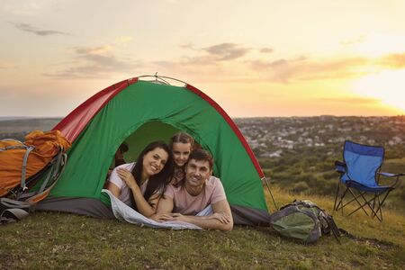Happy family with cute child on camping trip relaxing inside tent. Caring parents and their daughter relaxing at campsite during sunset