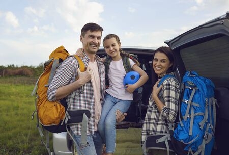 Smiling family of travelers by car standing in nature in summer. Mother and father with backpacks dochb prepared hiking camping in the countryside.