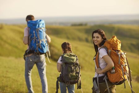 Family of travelers with backpacks walk along the grass in the mountains on nature in summer. Mother tourist is smiling, waving his hand, looking at the camera, is going with the rebknkm and his wife to the camping. Banque d'images