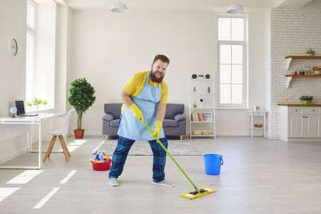 Funny fat man in an apron and yellow cleaning gloves is cleaning the house in the room.