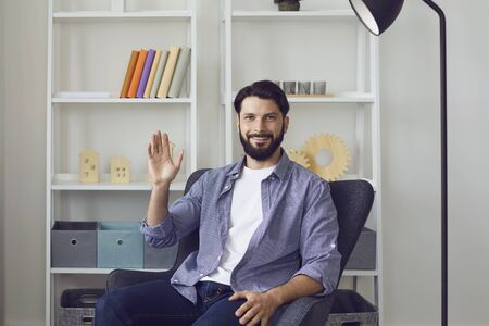 Handsome young man talking to friend, family or business partner online from home. Happy guy looking at camera and waving his hand