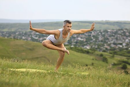 Sporty man doing yoga practice on mountain top. Peaceful guy enjoying his training surrounded by beautiful nature. Healthy lifestyle and sports