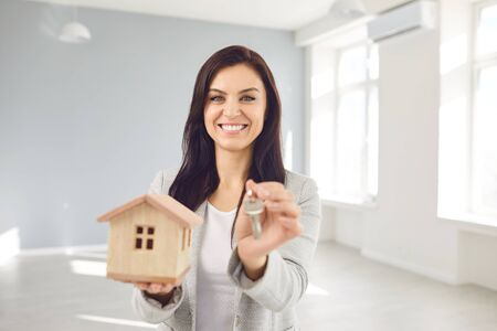 Woman seller broker realtor agent is a realtor with keys in hand against the background of a white real estate room apartment home. Sale purchase rent real estate mortgage.