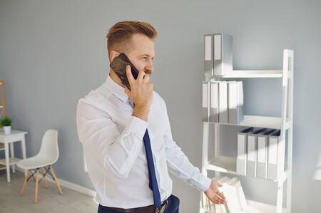 Adult focused bearded man in white shirt and blue tie speaking via smartphone looking away in office