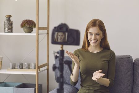 Blogger vlogger girl speaks to the camera while sitting on a sofa in a room at home. A young youthful girl talks gesticulating with his hands indoors.