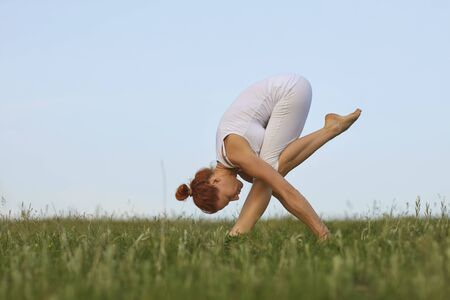 Concentrated young woman practicing morning yoga on green meadow, empty space. Beautiful girl doing forward bend exercise outdoors Stok Fotoğraf