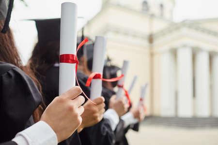 Graduates with diplomas in front of the university. The concept of training, education, graduates.
