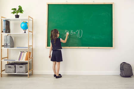 Back to school. Rear view of a schoolgirl in chalk writes on a school chalkboard in class. Training education care parenting lessons training lecture for children of students at school lyceum. Stock Photo