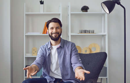 Smiling young caucasian man with dark beard video call looking at camera sitting in living room armchair with hands open in friendly welcome hug gesture. Hospitality, friendship and guest warm welcome concept. Reklamní fotografie