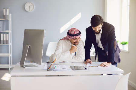 Arab and european businessman confident working in a white office. Businesspeople work startup business project merge business meeting in a modern business center.
